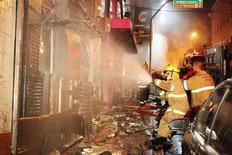 Des pompiers luttant contre un incendie dans une discothèque de la ville de Santa Maria, dans le sud du Brésil. Au moins 232 ont été tuées, piétinées dans la cohue ou asphyxiées. /Photo prise le 27 janvier 2013/REUTERS/Germano Roratto/Agencia RBS