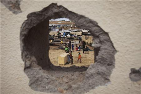 A fish market is seen through a hole in the wall in Konna, Mali, January 27, 2013. REUTERS/Joe Penney