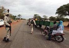 A Malian soldiers gestures at a check point at Thy, 15km away from Sevare, January 27, 2013. REUTERS/Eric Gaillard