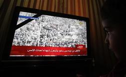 Retransmission TV desobsèques de trente-trois Egyptiens tués samedi lors de violences la veille dans la ville de Port-Saïd. Quatre autres personnes ont été tuées dimanche lors des obsèques. /Photo prise le 27 janvier 2013/REUTERS/Amr Abdallah Dalsh