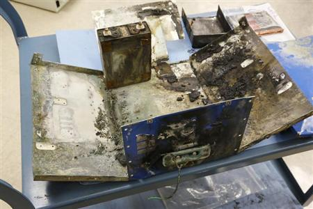 National Transportation Safety Board investigators display the exterior case of a thermal-damaged lithium ion battery, as a part of their ongoing investigation into why the battery caught fire in a Japan Airlines' 787 parked at Boston Logan International Airport January 7, at their labs in Washington, January 24, 2013. REUTERS/Jonathan Ernst