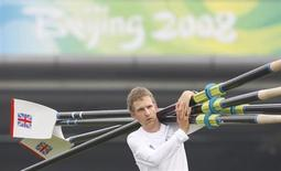 Britain's Men's Eight rowing coxman Acer Nethercott carries oars to the water for a training session at Shunyi Olympic Rowing-Canoeing Park north of Beijing in this file photo taken August 7, 2008. REUTERS/Darren Whiteside