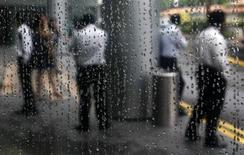 Office workers are reflected in a rain-covered window as they stand at the lobby of a building in Singapore's financial district March 16, 2009. REUTERS/Vivek Prakash