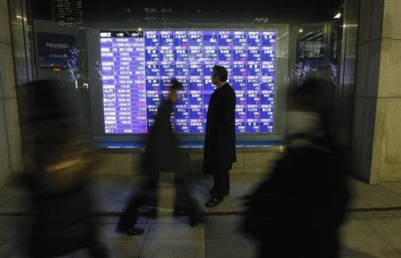 A man looks at a stock index board in Tokyo January 22, 2013. REUTERS/Kim Kyung-Hoon