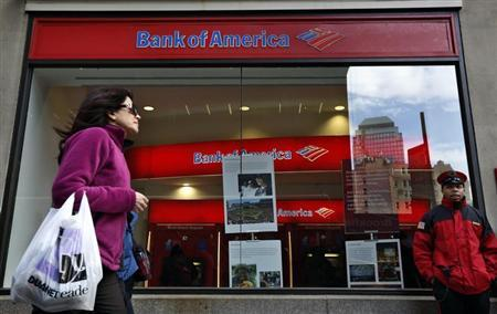 A woman walks past as customers use ATMs at a Bank of America banking center in New York's financial district January 17, 2013. REUTERS/Brendan McDermid