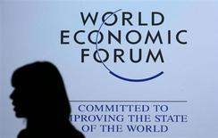 A delegate is silhouetted as she passes by a sign for the annual meeting of the World Economic Forum (WEF) in Davos January 26, 2013. REUTERS/Pascal Lauener (SWITZERLAND - Tags: POLITICS BUSINESS)