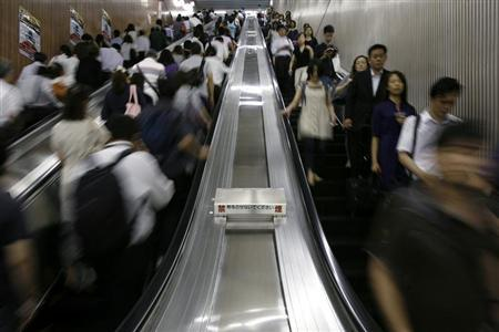 Commuters ride escalators at a subway station in Tokyo August 12, 2009. REUTERS/Stringer