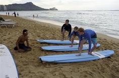 1月24日、米ハワイ州の観光当局は、2012年の訪問客が約800万人に上り、過去最高を記録したと発表。写真はワイキキビーチでサーフィンのレッスンを受ける観光客。昨年12月撮影(2013年 ロイター/Larry Downing)