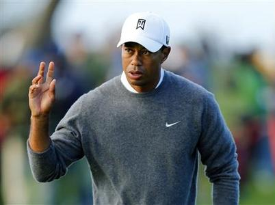 U.S. golfer Tiger Woods waves to fans after making par on the fifth hole during the weather-delayed fourth round play at the Farmers Insurance Open in San Diego, California, January 27, 2013. REUTERS/Mike Blake