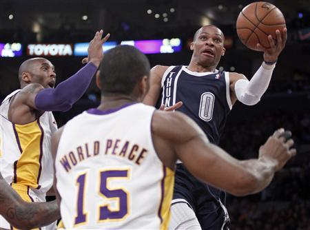 Oklahoma City Thunder guard Russell Westbrook (0) lets go a shot with Los Angeles Lakers guard Kobe Bryant (24) and Lakers forward Metta World Peace (15) defending during the first half of their NBA basketball game in Los Angeles, California January 27, 2013. REUTERS/Alex Gallardo
