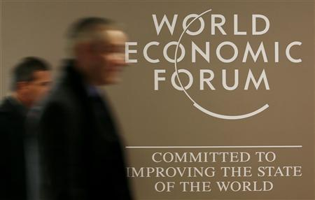 Men walk past the official logo of the World Economic Forum (WEF) inside the Congress Hall at the Swiss Alpine resort of Davos January 21, 2013. REUTERS/Pascal Lauener