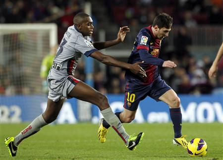 Barcelona's Lionel Messi (R) eludes Osasuna's Raoul Loe during their Spanish First division soccer league match at Camp Nou stadium in Barcelona, January 27, 2013. REUTERS/Albert Gea