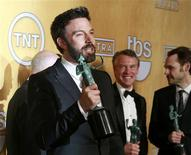 "Director and actor Ben Affleck holds the award for outstanding performance by a cast in a motion picture for ""Argo"" at the 19th annual Screen Actors Guild Awards in Los Angeles, California January 27, 2013. In the background are Tate Donovan and Christopher Denham (R). REUTERS/Adrees Latif"