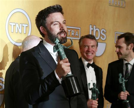 Director and actor Ben Affleck holds the award for outstanding performance by a cast in a motion picture for ''Argo'' at the 19th annual Screen Actors Guild Awards in Los Angeles, California January 27, 2013. In the background are Tate Donovan and Christopher Denham (R). REUTERS/Adrees Latif