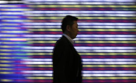 A man walks past a board showing graphs of Japan's stock price indexes outside a brokerage in Tokyo June 5, 2012. REUTERS/Toru Hanai/Files