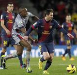 Lionel Messi marcó cuatro goles para el líder Barcelona y Cristiano Ronaldo logró un 'hat-trick' para el Real Madrid en sus partidos de Liga, días antes de que los dos rivales se encuentren a mitad de semana en semifinales de la Copa del Rey. En la imagen, Lionel Messi (D) elude a Raoul Loe del Osasuna durante el partido de Liga en el estadio Nou Camp, en Barcelona, el 27 de enero de 2013. REUTERS/Albert Gea