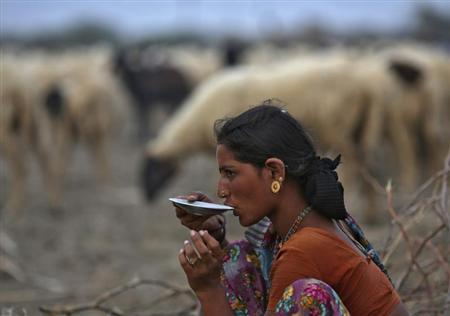 A village woman drinks tea after she migrated due to shortage of water on the outskirts of Sami town in Gujarat August 6, 2012. REUTERS/Ahmad Masood/Files