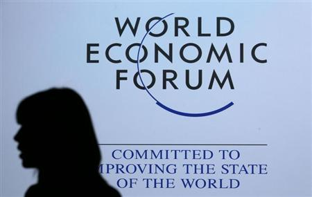 A delegate is silhouetted as she passes by a sign for the annual meeting of the World Economic Forum (WEF) in Davos January 26, 2013. REUTERS/Pascal Lauener