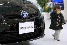 Un bimbo cammina vicino ad un modello Toyota Prius. REUTERS/Kim Kyung-hoon/Files