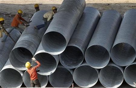Labourers work on steel pipes at a construction site of an overhead flyover in Chennai January 21, 2010. REUTERS/Babu/Files