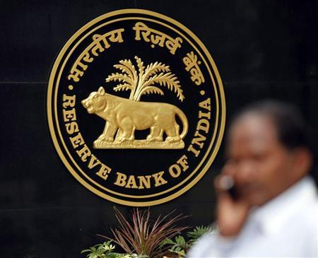 A man talks on his mobile phone as he walks past the logo of the Reserve Bank of India (RBI) inside its head office in Mumbai June 14, 2010. `REUTERS/Rupak De Chowdhuri/Files