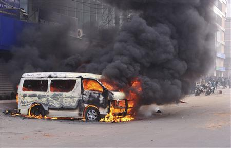 A minibus is set ablaze during a clash between Islamist activists and police in Dhaka January 28, 2013. REUTERS/Stringer
