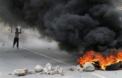 A child runs towards a burning barricade during a strike by farm workers at De Doorns on the N1 highway, linking Cape Town and Johannesburg, in this January 9, 2013 file photo. REUTERS/Mike Hutchings/Files