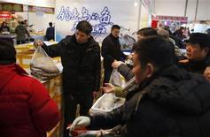 La búsqueda de la autosuficiencia en la producción de alimentos ya no es posible en China porque la creciente demanda y la rápida urbanización avivan los apetitos, dijo un alto cargo del Gobierno, en las declaraciones más directas hasta ahora sobre un posible incumplimiento del objetivo de la autosuficiencia. En la imagen, varios clientes compran pescado en Shanghái el 26 de enero de 2013. REUTERS/Aly Song