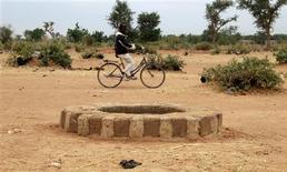 Tropas malienses apoyadas por soldados franceses buscaban el lunes en Tombuctú a rebeldes islamistas tras tomar el aeropuerto y rodear la antigua localidad turística y comercial del Sáhara en una ofensiva relámpago contra los combatientes aliados de Al Qaeda en el norte de Mali. En la imagen, un hombre pasa en bicicleta junto al pozo donde se hallaron los cuerpos de varios integristas islámicos el 28 de enero de 2013, según el director de derechos humanos de Human Rights Watch, Philippe Bolopion. REUTERS/Eric Gaillard