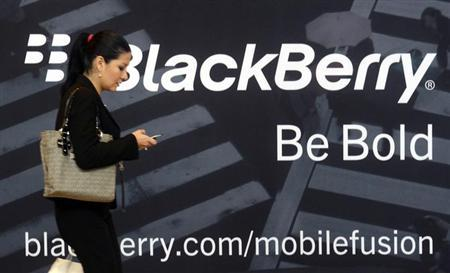 A woman uses her mobile phone at the Blackberry World Event in Orlando May 1, 2012. REUTERS/David Manning/Files