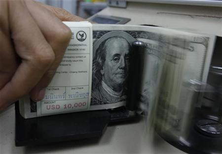 A bank employee counts U.S. hundred dollar bills at Kasikornbank in Bangkok January 21, 2010. REUTERS/Sukree Sukplang/Files