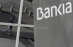 Bankia ha reducido a cero su autocartera después de vender un saldo neto de 86,12 millones de acciones, lo que equivale a una participación del 4,319 por ciento, según los registros de la Comisión Nacional del Mercado de Valores (CNMV). En la imagen, un hombre reflejado en las ventanas de la sede de Bankia en Madrid el 28 de noviembre de 2012. REUTERS/Andrea Comas