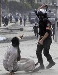Un policía antidisturbios usa una vara contra un manifestante durante unos enfrentamientos cerca de la plaza Tahrir en El Cairo, ene 28 2013. Un hombre murió baleado el lunes en el quinto día de una ola de violencia en Egipto que ha dejado un saldo de 50 muertos y llevó al presidente islamista a declarar el estado de emergencia, en un intento por poner fin a una ola de agitación que sacude al mayor país del mundo árabe. REUTERS/Amr Abdallah Dalsh