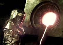"""Рабочий на следит за выплавкой золота на золотодобывающем предприятии Кумтор в Киргизии 4 февраля 2004 года. Киргизия потребовала больше платежей от канадской Centerra Gold, разрабатывающей здесь крупнейшее месторождение золота в - Кумтор и высказалась за отмену """"особого"""" соглашения и переход к уплате всех видов платежей на общих для всех инвесторов основаниях. REUTERS/Shamil Zhumatov"""