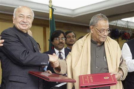 India's Home Minister Sushil Kumar Shinde (L) shakes hands with Bangladesh's Minister for Home Affairs Mohiuddin Khan Alamgir as they pose for the media after signing a treaty in Dhaka January 28, 2013. REUTERS/Andrew Biraj