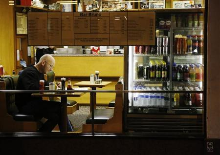 A man sits in a cafe in London November 13, 2012. REUTERS/Luke MacGregor