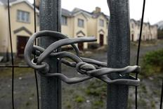 An electrical cable is used to secure a security fence surrounding Cnoc an Iuir, an empty and unsold housing development in the village of Drumshanbo, County Leitrim in a January 28, 2012 file photo. Ireland's recovery story could yet take a nasty plot turn unless the European Central Bank agrees to cut the cost of bailing out its banks. Ireland's lenders, at the heart of the country's financial woes, may yet have to tap the state for more cash, jeopardising Dublin's plans to exit an EU-IMF bailout and give the euro zone its first post-crisis success. REUTERS/Cathal McNaughton/files