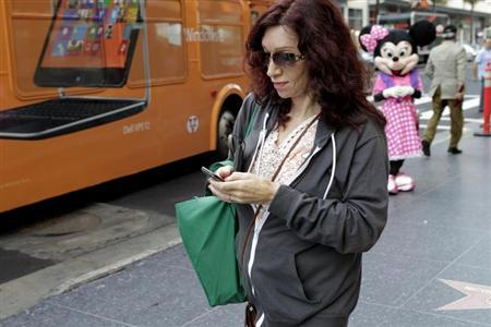 An unidentified woman texts on her mobile phone as she walks along Hollywood Boulevard in Hollywood, California December 3 2012. REUTERS/Fred Prouser/Files
