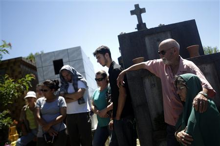 Relatives of Paula Simone Melo Prates, who died during the fire at Boate Kiss nightclub, attend her funeral at the cemetery in the southern city of Santa Maria, 187 miles (301 km) west of the state capital Porto Alegre, January 28, 2013. The nightclub fire killed at least 233 people in southern Brazil on Sunday when a band's pyrotechnics show set the building ablaze and fleeing partygoers stampeded toward blocked exits in the ensuing panic, officials said. REUTERS/Ricardo Moraes (BRAZIL - Tags: DISASTER)