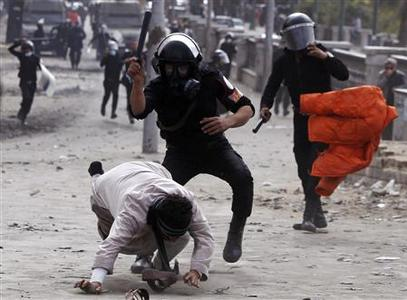Riot policemen beat a protester opposing Egyptian President Mohamed Mursi, during clashes along Qasr Al Nil bridge, which leads to Tahrir Square in Cairo January 28, 2013. REUTERS/Amr Abdallah Dalsh