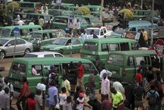 """Files de taxis près d'un marché dans la capitale nigériane Abuja. Paris déconseille à ses ressortissants de se rendre dans le nord du Nigeria à la suite de menaces directes formulées par """"des groupes terroristes nigérians"""" en représailles à l'intervention militaire française au Mali. /Photo d'archives/REUTERS/Akintunde Akinleye"""