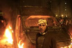 A protester stands in front of a burning riot police vehicle after it was seized on the Kasr Elnile bridge in Cairo January 28, 2013. A man was shot dead on Monday in a fifth day of violence that has killed 50 Egyptians and prompted the Islamist president to declare a state of emergency in an attempt to end a wave of unrest sweeping the biggest Arab nation. REUTERS/Mohamed Abd El Ghany (EGYPT - Tags: POLITICS CIVIL UNREST)