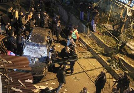Security policemen inspect a damaged car in the suburbs of Beirut January 28, 2013. . REUTERS/Hassan Shaaban (LEBANON - Tags: CIVIL UNREST POLITICS)