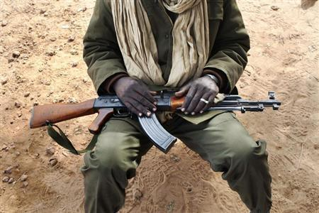 A Malian soldier holds an AK-47 in his lap at a military checkpoint in Diabaly January 26, 2013. REUTERS/Joe Penney