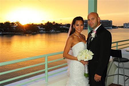 Lazaro Sopena poses with Hann Dinh on their wedding day in Miami Beach, Florida, in this July 2, 2011 handout photo. Sopena opted to take his wife's last name only to be accused of fraud by the state's Department of Motor Vehicles. The South Florida real estate investor lovingly offered to change his name following his 2011 marriage to Hann Dinh in order to help his wife's family perpetuate their family surname. Dinh, who was born in Vietnam, is from a family of all girls and only one son. REUTERS/Jay Nguyen/Handout