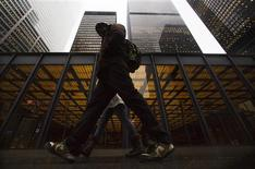 "A man walks in front of buildings in the financial district in Toronto, January 28, 2013. Moody's Investors Service has cut the ratings of six Canadian financial institutions, including the previously ""Aaa"" rated Toronto-Dominion Bank, due to concerns about rising consumer debt and high housing prices. TD, the only publicly traded bank that still carried Moody's top rating, was downgraded, along with Bank of Nova Scotia , Canadian Imperial Bank of Commerce, Bank of Montreal, National Bank of Canada and Caisse Central Desjardins, Canada's largest association of credit unions, Moody's said on Monday. REUTERS/Mark Blinch"