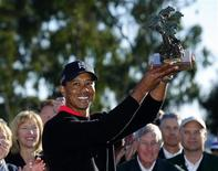 U.S. golfer Tiger Woods holds up the trophy after winning at the Farmers Insurance Open in San Diego, California January 28, 2013. Woods withstood a late bogey, double-bogey, par, bogey wobble in strengthening winds to clinch his 75th PGA Tour title by four shots at the fog-delayed Farmers Insurance Open on Monday. REUTERS/Mike Blake