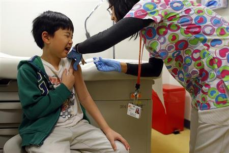Chihn Ha, eight year old, gets an influenza vaccine injection from nurse Nho Nguyen (R) during a flu shot clinic at Dorchester House, a health care clinic, in Boston, Massachusetts January 12, 2013. REUTERS/Brian Snyder/Files