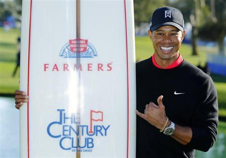 U.S. golfer Tiger Woods poses with a surf board as one of his prizes after winning the Farmers Insurance Open in San Diego, California January 28, 2013. Woods withstood a late bogey, double-bogey, par, bogey wobble in strengthening winds to clinch his 75th PGA Tour title by four shots at the fog-delayed Farmers Insurance Open on Monday. REUTERS/Mike Blake