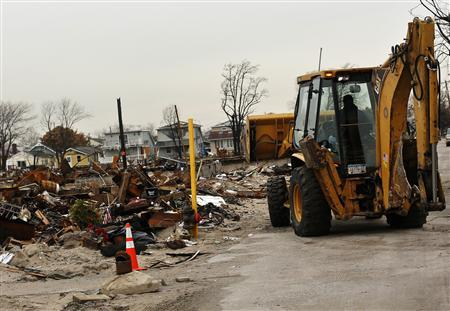 A vehicle makes its way near homes devastated by fire and the effects of Hurricane Sandy in the Breezy Point section of the Queens borough in New York January 15, 2013. REUTERS/Shannon Stapleton